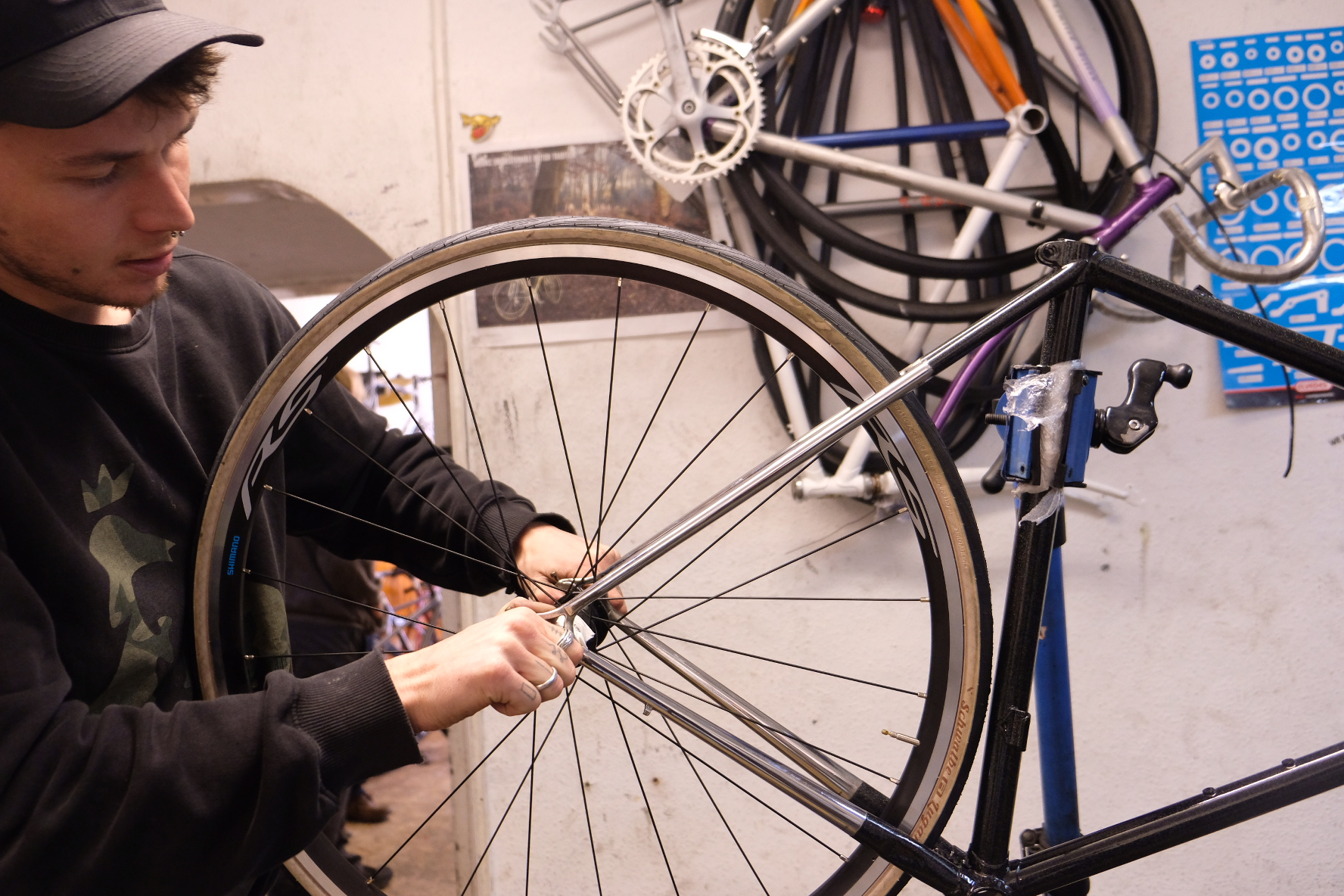 Shop manager Barney works on a classic steel framed bicycle that is being carefully restored.