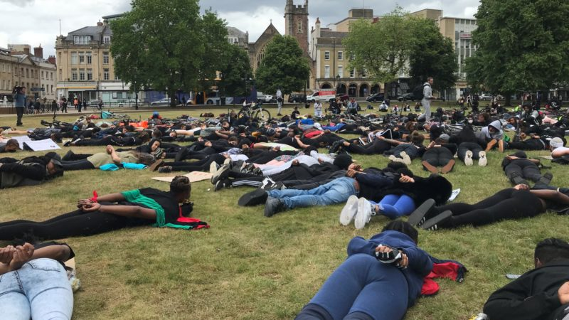Black Lives Matter protesters lie down with hands behind backs on College Green