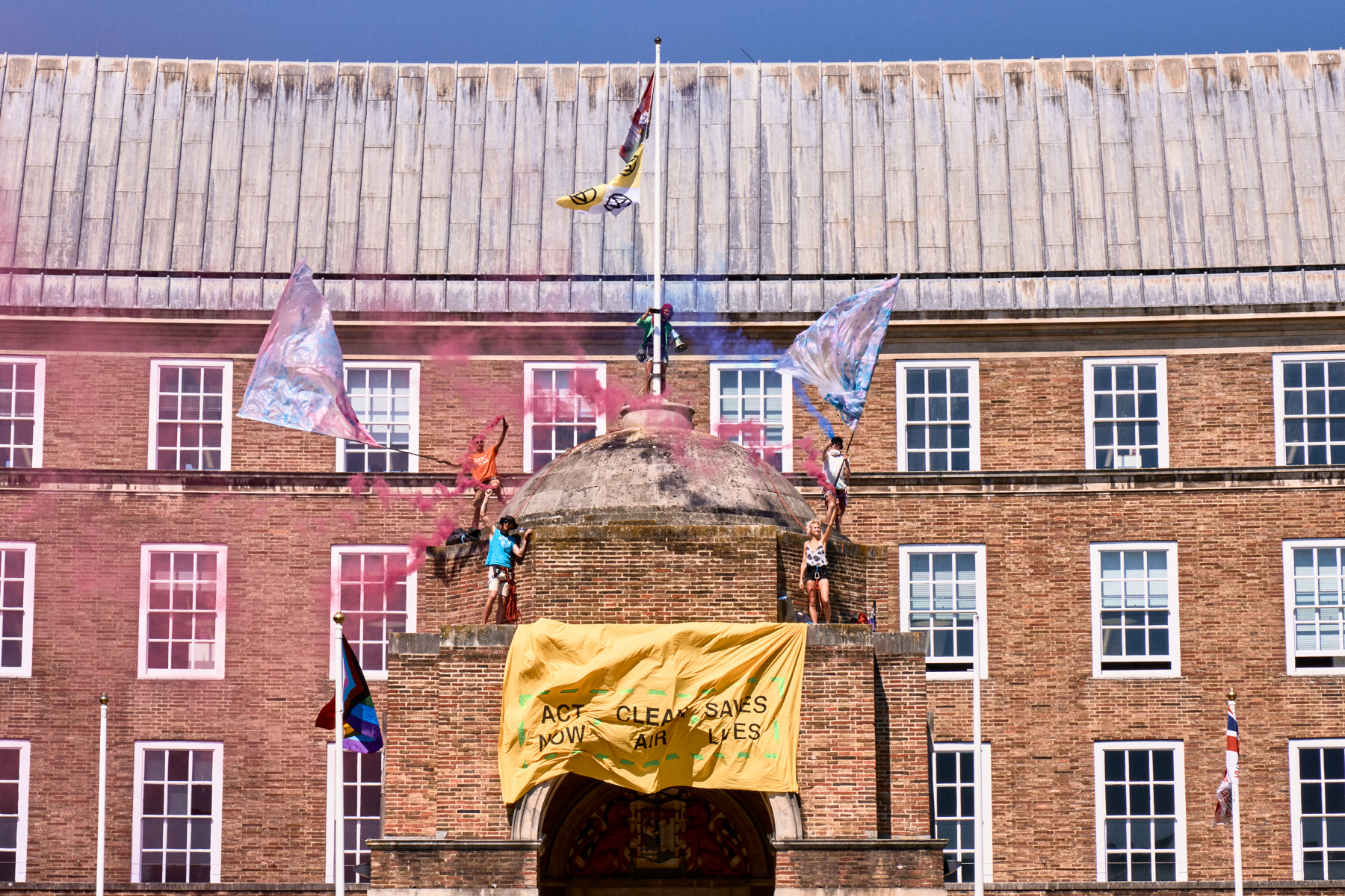 """Photo: Extinction Rebellion wave flags atop the roof of City Hall amidst colourful smoke from smoke bombs and a sign that imitates coronavirus messaging, saying """"Act Now, Clean Air, Save Lives""""."""