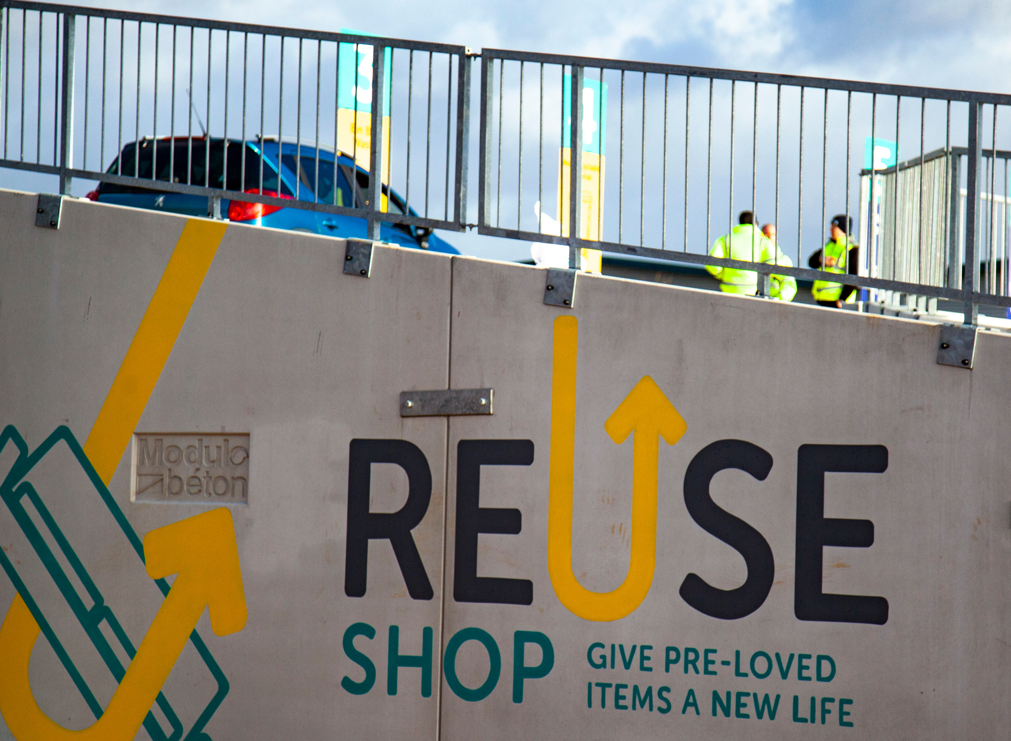 """Photo: Sign painted on side of concrete barriers saying """"Reuse Shop Give pre-loved items a new life"""""""