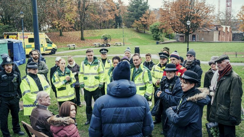 Photo: Actors dressed as ambulance workers, police, civilians, and the Skripals stand around a park bench in Castle Park with production crew.