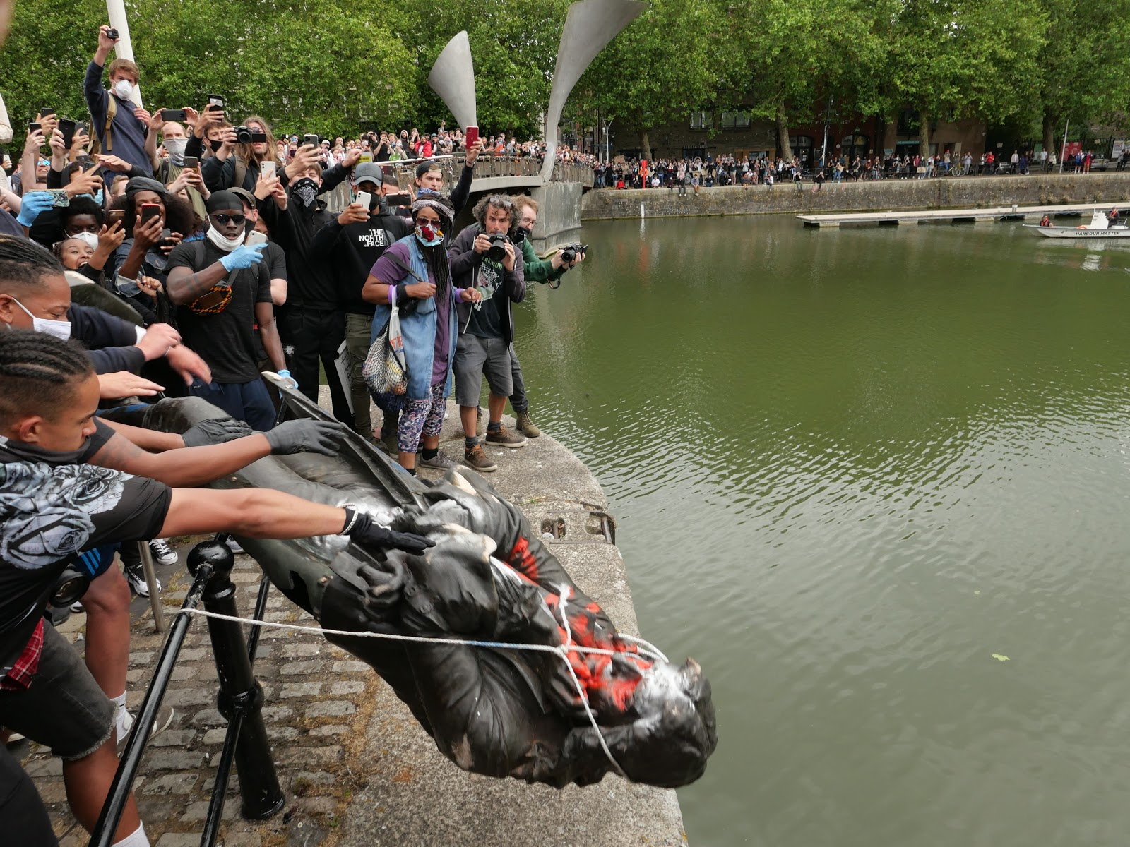 Photo: Crowds gather around the Floating Harbour and stand on Pero's Bridge as the statue of Edward Colston, covered in graffiti and with a rope around its neck is lifted over a fence to be thrown in to the water below.
